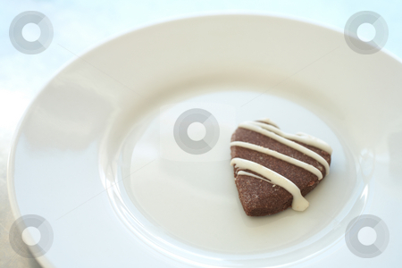 Cookie on a plate stock photo, The last heart shaped cookie on a white ceramic plate by Sean Nel