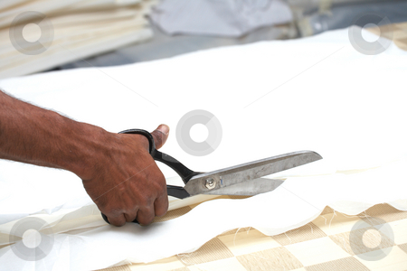 Man cutting fabric stock photo, Man cutting white material with industrial sewing scissors, on a cutting table (Shallow Depth of Field ? focus on scissors) by Sean Nel