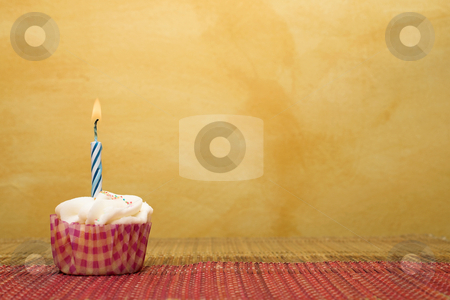 Cupcakes #1 stock photo, One cupcake on pink and brown table cloth in front of  wall - copy space by Sean Nel