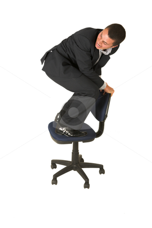 Businessman #237 stock photo, Businessman wearing a suit and a grey shirt.  Standing  on an office chair. by Sean Nel
