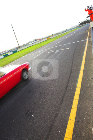 Speeding racer on racetrack stock photo, Final lap and checkered flag in front of the pit lane of Killarney Race Track in the Western Cape, South Africa. Cloudy and wet race day. red car racing by (movement on racer, road in focus) by Sean Nel