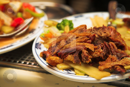 Plate of Chinese fried duck on a burner stock photo, Plate of Chinese Fried Duck. A Chinese food dish of fried noodles with sweet and sour sauce, salad, and pieces of cheese  as well as some vegetables like onions and carrots. Image taken inside a Chinese restaurant. by Sean Nel