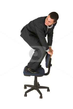 Bussinessman #236 stock photo, Businessman wearing a suit and a grey shirt.  Making a stunt on an office chair. by Sean Nel