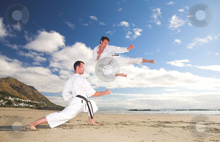 Men practicing Karate on the beach stock photo, Young adult men with black belt practicing on the beach on a sunny day. The man doing the flying kick in the background has movement. Focus on the standing man by Sean Nel