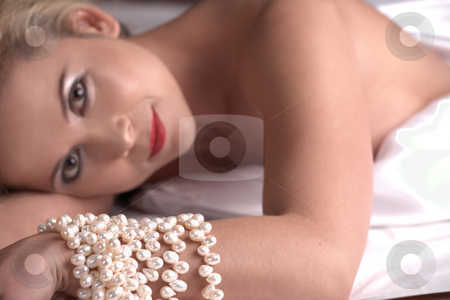 Nude adult woman stock photo, Sensual naked young blonde adult Caucasian woman, wrapped in a satin, silk sheet on a bed in her bedroom. High contrast lighting - Shallow Depth of Field, focus on pearls by Sean Nel