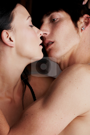Intimate young lovers stock photo, Young adult Caucasian couple in passionate embrace and undressing each other during sexual foreplay by Sean Nel