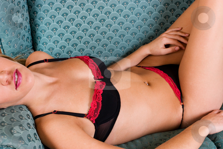 Lingerie #45 stock photo, Beatiful blonde woman lying on blue couch in black and red lingerie by Sean Nel