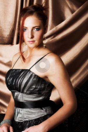 Sexy adult woman stock photo, Beautiful young sexy adult Redheaded woman with long auburn hair, in formal black dress on a textured silk background ? Hard light, high key. Defucussed by Sean Nel