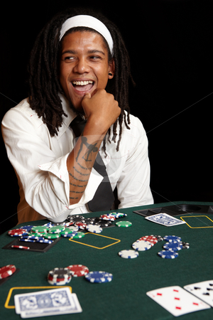 Card gambling stock photo, Young African man with dreadlocks playing cards, chips and players gambling around a green felt poker table. Shallow Depth of field by Sean Nel