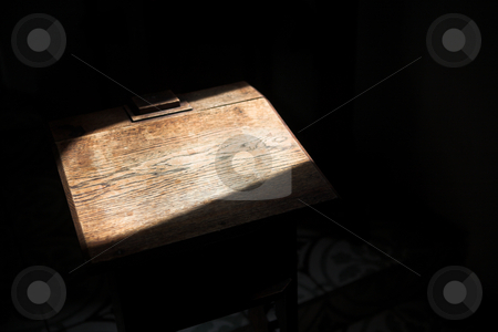 Empty wooden pedestal stock photo, Old wooden pedestal standing empty inside a small chapel in a lone sunbeam from an open window by Sean Nel