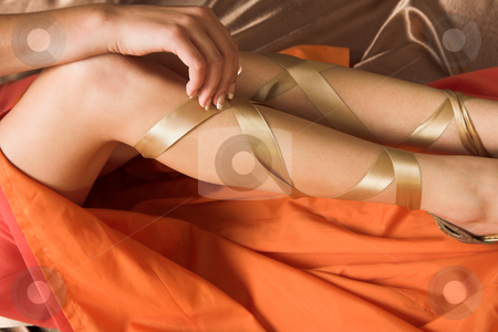 Sexy legs stock photo, Sexy legs of Caucasian adult woman in luxurious orange silk dress by Sean Nel