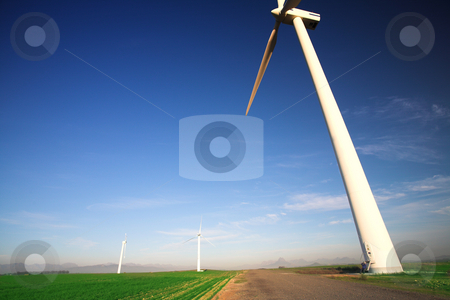 Wind powered turbine stock photo, Wind powered electricity generator standing against the blue sky in a green field on the wind farm. by Sean Nel
