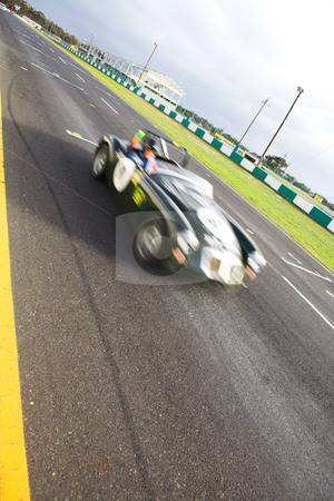 Speeding racer on racetrack stock photo, Starting grid in front of the pit lane of Killarney Race Track in the Western Cape, South Africa. Cloudy and wet race day. Green car racing by (movement on racer, road in focus) by Sean Nel