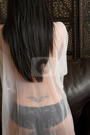 Woman in Babydoll stock photo, Sexy adult woman in white babydoll and black lacy lingerie. Tattoo on the back shows through the material. by Sean Nel