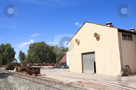 Industrial type warehouse and factory stock photo, Rusted metal mining wagons standing outside an industrial warehouse with train tracks running in front of the building. Blue sky and sunny day by Sean Nel