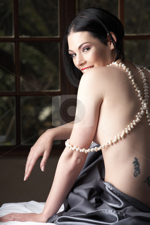 Nude adult woman stock photo, Sensual naked young Black haired adult Caucasian woman, wrapped in a charcoal colored satin, silk sheet on a bed in her bedroom. Fresh water pearl necklace by Sean Nel