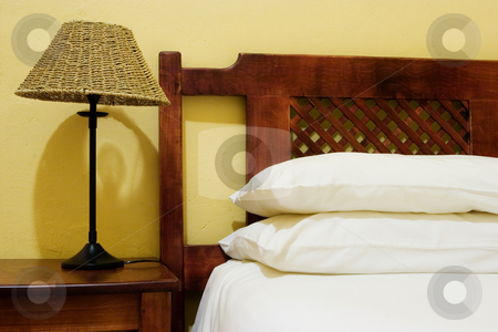 Interior #6 stock photo, Interior of room with bedside lamps, wooden bed and white duvet cover by Sean Nel
