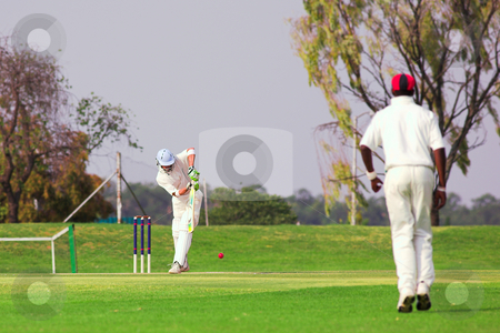 Cricket player hitting ball stock photo, Cricketers playing in the late afternoon, Batsman hitting ball, fielder running forward on green cricket pitch - Overcast Day, before the storm by Sean Nel