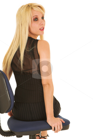 Young blonde businesswoman isolated on white stock photo, A young blonde businesswoman with red lips and green eyes in a formal black pinstripe suite with pencil skirt, sitting on an office chair - isolated on a white background by Sean Nel