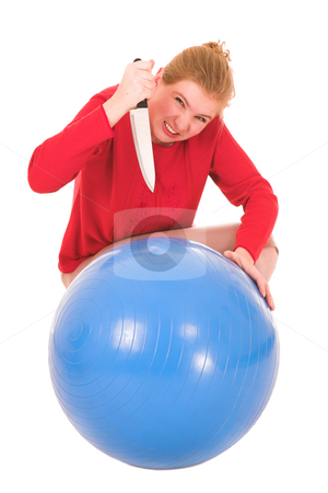 Blonde Murderess woman stock photo, Frustrated blonde middle aged woman with a large carving knife about to kill a yoga ball by Sean Nel