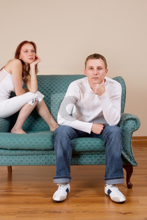 Trudy-Lee & Tommy #8 stock photo, Woman and boyfriend sitting on couch - bored by Sean Nel