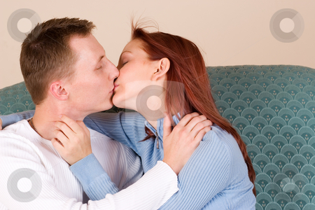 Trudy-Lee & Tommy #12 stock photo, Woman and boyfriend kissing on couch by Sean Nel