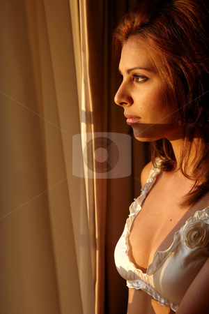 Woman in Lingerie stock photo, Young sexy Caucasian adult woman in lingerie in a bedroom setting, standing by a window at sunset by Sean Nel