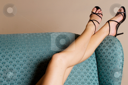 Legs #4 stock photo, Beautiful, long legs with black sandals on a blue couch by Sean Nel