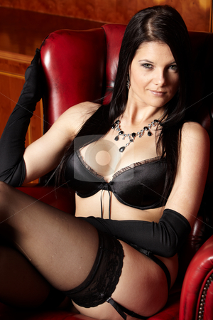 Woman in Lingerie stock photo, Sexy young adult caucasian woman in black lingerie sitting in an executive office with a red leather highback chair, with high contrast lighting by Sean Nel