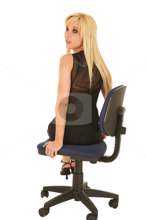 Young blonde businesswoman isolated on white stock photo, A young blonde businesswoman in a formal black pinstripe suite with pencil skirt, sitting on an office chair - isolated on a white background by Sean Nel