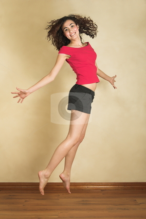 Young adult woman stock photo, Portrait of a beautiful young adult Caucasian woman with light skin and curly brown hair, brown eyes and pink lips, wearing a red top and black shorts. Jumping in the air by Sean Nel