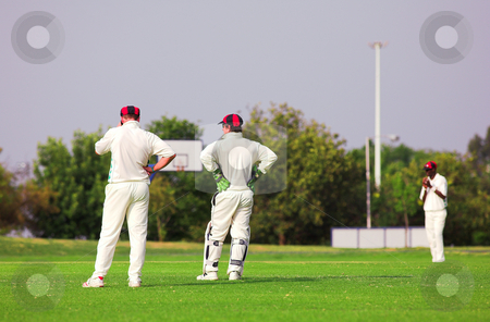 Cricket players standing around waiting on the field stock photo, Cricket players standing on the cricket pitch waiting for the game to resume. Wicketkeeper talking to fielder, all players wearing white by Sean Nel