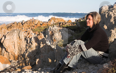 Beautiful adult woman sitting on the beach stock photo, Beautiful adult woman with short hair sitting on the beach in the last rays of the setting sun, smiling and looking up. Coastal rocks and the ocean in the background by Sean Nel