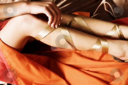 Sexy legs stock photo, Sexy legs of Caucasian adult woman in luxurious orange silk dress by Sean Nel