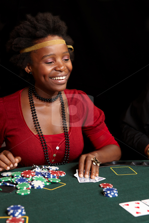 Card gambling stock photo, African Woman playing cards, chips and players gambling around a green felt poker table. Shallow Depth of field by Sean Nel