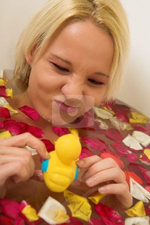 Woman #146 stock photo, Nude woman in a bath, playing with a plastic toy duck. by Sean Nel