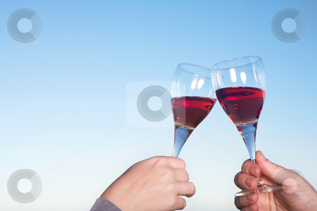 Wineglasses toasted stock photo, Couple toasting wineglasses against a blue sky on a summers day by Sean Nel