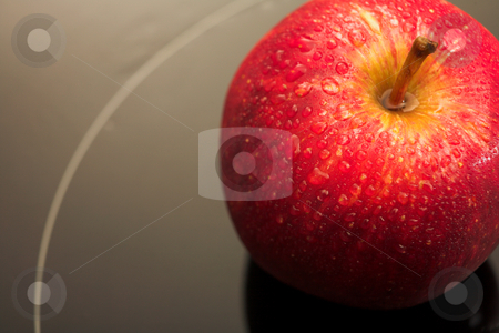 Red Apple on black glass top stock photo, Close up view of a shiny red apple on a reflective black glass working surface with water drops on the surface (very shallow Depth of Field  by Sean Nel