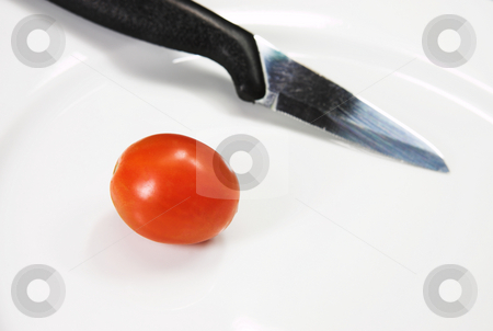 Knife stock photo, A knife and a cherry tomato on a white plate. by Sean Nel