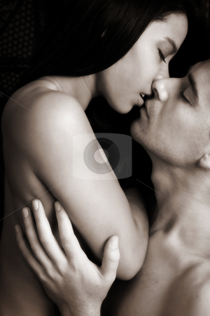 Intimate lovers embrace stock photo, Multi-ethnic couple in passionate embrace and undressing each other during sexual foreplay - High Contrast Black and White by Sean Nel