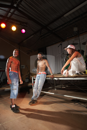 Three hip-hop dancers stock photo, Three freestyle hip-hop dancers standing around after a training session. Two young adult males and a female in a home training studio with stage and instruments standing around. by Sean Nel