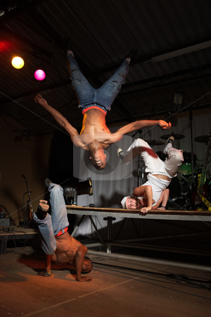 Three hip-hop dancers stock photo, Three freestyle hip-hop dancers in a dancing training session. Two young adult males and a female in a home training studio with stage and instruments. Lit with spotlights. Movement on edges of dancers by Sean Nel