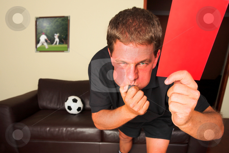 Referee in sitting room blowing whistle with red card  stock photo, A typical sports fan as a referee in his sitting room, blowing a whistle and showing a red card or penalty card to send off an offending player. Cricketers on image in background by same artist. Soccer ball on the leather couch. Shallow DOF, Focus on hand with red card. by Sean Nel