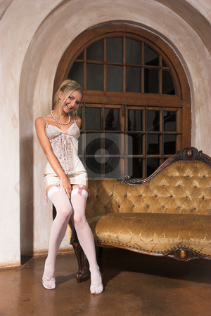 Lingerie #21 stock photo, Woman with lace up pink lingerie and garter sitting on couch by Sean Nel