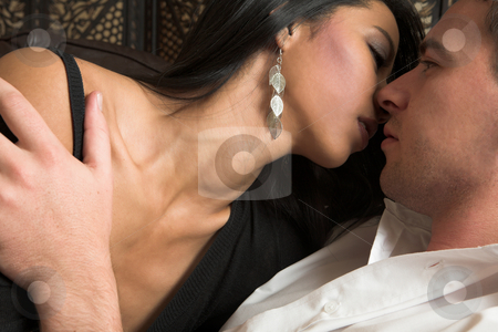 Intimate lovers embrace stock photo, Multi-ethnic couple in passionate embrace and undressing each other during sexual foreplay by Sean Nel