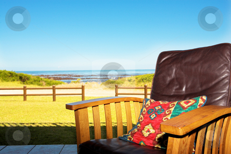 Comfortable chair on patio at seaside stock photo, A comfortable leather chair on a patio at a seaside residence or holiday home. Shallow depth of field. Focus on front armrest by Sean Nel