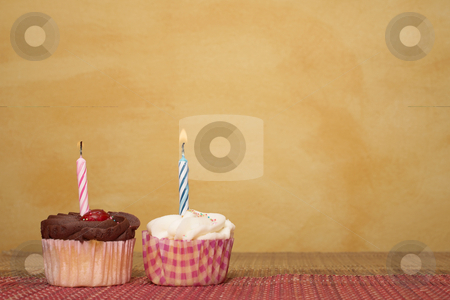 Cupcakes #5 stock photo, Two cupcakes on pink and brown table cloth in front of  wall - copy space by Sean Nel