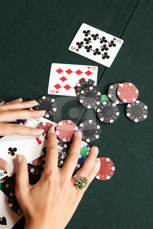 Card gambling stock photo, Playing cards, chips and player pulling winnings to herself on a green felt poker table by Sean Nel