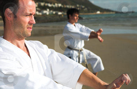 Men practicing Karate on the beach stock photo, Young adult men with black belt practicing a Kata on the beach on a sunny day (man in background more visible) by Sean Nel