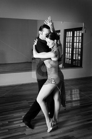 Two ballroom dancers practicing in their studio stock photo, A young adult couple dancing and practicing ballroom dancing together in a studio - Focus on woman, Black and white - high key efect by Sean Nel